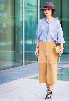 An oversized striped blouse is worn with a suede midi skirt, lace-up heels, and a fedora
