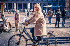 Unos vaqueros, un abrigo color camel, unas botas de ante, unas gafas de sol y vamos perfectos para pasear en bici por Madrid.