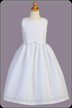 This lovely white cotton Communion dress features beautiful embroidered and eyelet flowers throughout, sleeveless bodice, center bow at the waist with a tie back satin sash and t-length skirt. Girls First Communion Dresses, Holy Communion Dresses, Baptism Dress, Little Girl Dresses, Flower Girl Dresses, Frock Design, Girl Fashion, Fashion Dresses, Casual Dresses