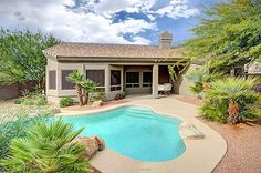 Retreat out back for fun or relaxation. The sparkling play pool is heated for year-round use.  Newer Kool decking and covered dining patio. #outdoor #resortstyle #sparklingpool #backyard #palmtrees #heatedpool