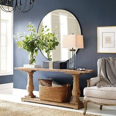 We have entryway envy after seeing this column table! Combine a unique wood table, round mirror, and an accent chair to achieve the same gorgeous look. #WayfairCanada #Greyleigh