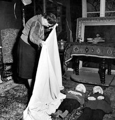 German woman using sheet to cover bodies of 2 children who were killed by their mother who then killed herself after hearing that her husband had lost his life fighting on the outskirts of the city after its liberation by Allied forces, 1945, by Margaret Bourke-White