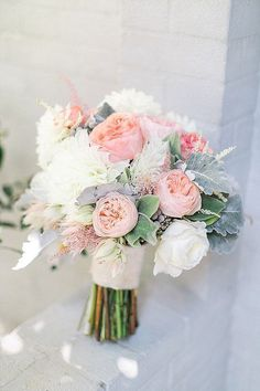 Cream hydrangeas, dusty pink garden roses, ivory spray roses, and grey dusty miller wrapped in champagne ribbon with the stems showing #weddingbouquet #bouquet