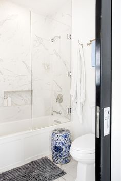 White marble bathroom design with with blue and white china stool | Pamela Dailey Design
