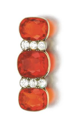 FIRE OPAL AND DIAMOND BROOCH, EARLY 20TH CENTURY Set with three cushion-shaped fire opals, and circular-cut diamonds.