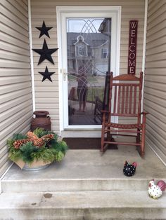 "My primitive porch. Barn stars, a nice big ""welcome"" sign, a rusty old milk can, and a wooden rocking chair."