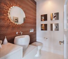 Center of attention in this bathroom is its round mirror with the shell- decorated lighting behind it./ Photo by Jeri Koegel Photography