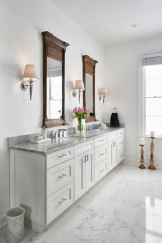 This traditional white master bathroom features white Shaker-style cabinetry with Carrara marble countertops. Durable porcelain tile floors mimic the Carrara marble pattern. The white space is contrasted with rustic Restoration Hardware mirrors and chrome fixtures.