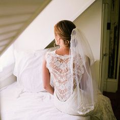Brides: Wedding Hairstyles that Work Well with Veils  - A Loose, Low Updo Wedding Hairstyle  Pull some front pieces out of this low twisted bun for a slightly undone look. The vintage-looking Chantilly lace fingertip veil adds romance and sophistication.  Brides.com