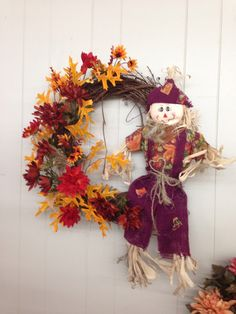 Fall scarecrow wreath with mixed mums and gold leaves.