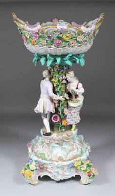 Meissen porcelain centre piece and separate stand modelled with figures supporting a pierced bowl.