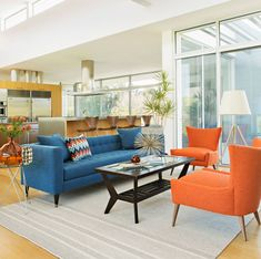 Cheerful Blue And Orange Living Room Will Be Favorite Space - living room with blue theme and orange blend of color on the beautiful blue sofa and unique orange chair