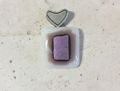 Fused glass necklace pendant with antique silver plated heart bail. Pendant fused with a white glass base and a purple accent topped with an