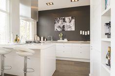 Wit hoogglans keuken met warm blad en mooie grijze muur.