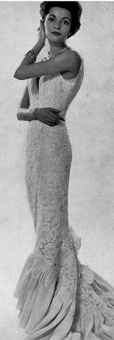 Model in exquisite slim evening gown of white lace over silk, ruffled hem extends into slight train, by Pierre Balmain, 1958 // photo by Georges Saad
