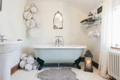 Roll top bath, claw foot tub decorated with white honeycomb and paper snowflake decorations | winter & christmas decor