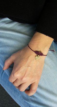 Ein geknüpftes **Armband** in tiefem Violettrot mit eingearbeitetem Anhänger aus Messing und Rocailles.  Es ist größenverstellbar und lässt sich somit individuell anpassen.  Hergestellt aus...