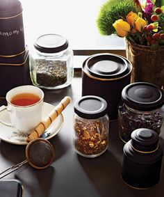 A chic way to update your jars and containers - Chatelaine. Spray paint lid black. Line the rim, top or base of the jars with a thick gold leaf pen.