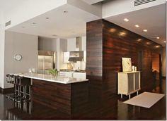 Sala e cozinha integradas através do revestimento de parede feito com madeira