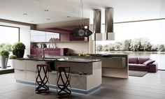 Plum purple units and breakfast bar stools give an unusual edge to this kitchen. The juicy hue warms up the predominantly cream décor.