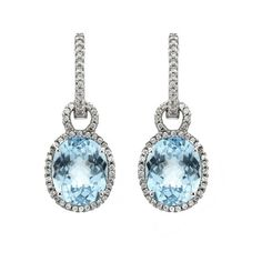 Blue Topaz Drop Earrings A pair of oval cut blue topaz drop earrings, combined weight 7.27cts, in a four claw setting surrounded by round brilliant cut diamonds, suspended from a diamond set hoop, combined weight 0.28ct, all mounted in an 18ct white gold setting.