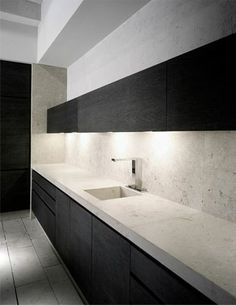 Kitchen in dark wood and natural stone. Joan Lao Design Studio.