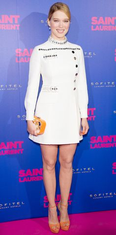 Lea Seydoux hit the Paris premiere of Saint Laurent in a white Swarovski crystal-embroidered military-style Miu Miu dress with an orange gem-encrusted Miu Miu box clutch and matching ankle-strap peep-toes.