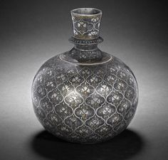 A Mughal silver- and brass-inlaid alloy Bidri Huqqa Base   Bidar, Deccan, 17th Century  the body of rounded form with narrow truncated neck slightly flaring towards rim, decorated in silver and brass inlay with a repeated design of floral motifs within cartouches   19 cm. high