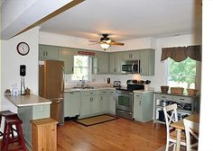 Green cabinets for a country kitchen with stainless steel appliances
