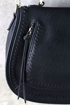 """Traveling the globe is as easy as picking a place on a map, and grabbing the Free Roam Black Purse! Structured vegan leather bag, with whip-stitched accents and a zippered kangaroo pocket at front and zipper pocket at back. Lift front flap from a hidden magnetic closure to reveal a roomy interior (with three additional pockets). Adjustable strap measures 50"""" at longest adjustment."""