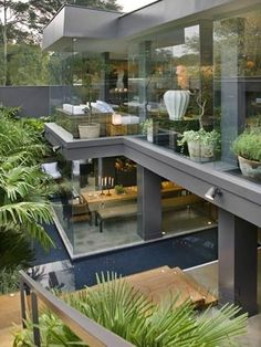 Modern house made primarily of glass and steel. Add lots of plants, some water and you have yourself luxury.