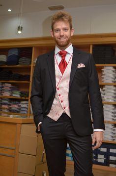 Traje basic negro con chaleco cruzado y motivo floral rojo, al tono de detalles y complementos.  www.sastreriacampfaso.es