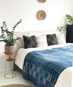 A classic African indigo textile is casually thrown over the bed to add pattern and color. The black and white tribal print mud cloth works well as draped ...
