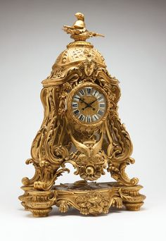 A LeRolle Freres Louis XV style ormolu mantle clock ::  Second half 19th century, Paris, the dial signed ''LeRolle Fres'', the movement stamped ''LeRolle Fres / Paris / 428'' and further stamped ''Medaille de Bronze / S. Marti et Cie.'', underside of base stamped ''L.R. 1066'', the gilt circular dial relief-decorated with scrolling foliage and chimeras and inset with white enamel Roman numeral cartouches surrounding twin key-wind apertures, within a hinged, circular glazed bezel in a waisted…