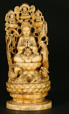 vory carving, Guanyin (or Quan Yin), Chinese, with signed base. Circa early 20th Century. Contains main Guanyin figure and three smaller Buddha figures praying at top. Dragon and phoenixbird carvings flank Guan Yin who is seated on traditional lotus leaf pedestal. The whole raised on a lotus leaf base. China c. 1900.