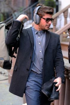 "Zac Efron flashes the peace sign as he walks to the set of ""Are We Officially Dating?"" filming in Greenwich Village in New York City"