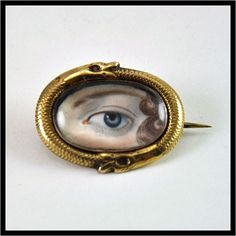 A nineteenth-century lover's-eye brooch, surrounded by a serpent, a symbol of eternity.