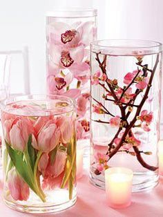centerpieces made from vases filled with silk flowers and a jug of distilled water