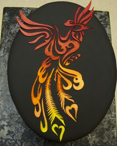 Phoenix Birthday Cake - Birthday cake for my father-in-law. Chocolate cake with dark chocolate frosting, covered with chocolate fondant that I tinted black. Phoenix and flames are tattoo designs I found on the web, and are made from gumpaste and painted with powdered food coloring.
