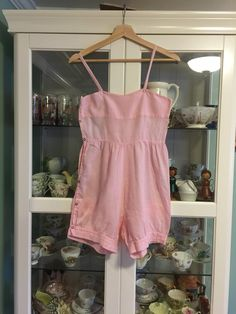 This was possibly a pre teen or teen romper. Homemade out of a cotton flour or feedsack . The marking on the sack still visible at the top. I think this may have been a project for a younger girl . The snaps go down the right side of the romper instead of the left. It is very soft pink cotton, six red snaps down the side and has a sweet shape. Good condition for its age. One tiny hole on the backside. No stains. Xs Measurements: Bust 30 Im a 31 and it fits me Waist 27 Thigh opening 20 From…