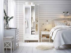 ミラーガラスの扉が付いたワードローブ、チェストとその上に取り付けたミラー、ベッドサイドテーブル、大きなベッドをすべて白で統一したカントリースタイルの広いベッドルーム。