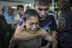 A Palestinian man comforts his son after they lost a relative in the attack on the U.N. school in the Gaza Strip. Poor souls.