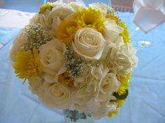 white hydrangea, white roses, yellow daisies, baby's breath and yellow ranunculus.