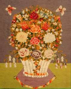 A soldier made woolwork picture depicting an abundant arrangement of flowers in a basket with two butterflies approaching. English circa 1860. Within a period maple veneered frame.