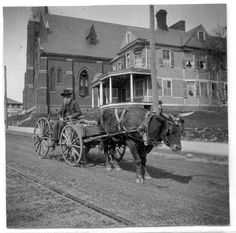 From Pack Library NC Collection: Photo of man in ox wagon moving along College St passing in front of the First Baptist Church  on the corner of Spruce and College Sts, and the Baptist parsonage (56 E College St; formerly the J. Rush Oates House). Oates came here ca 1890, owned the Legal Building and the Oates building, and moved to Gertrude Place in Grove Park in 1915. Third Baptist sanctuary shown here, built 1890s and demolished ca 1927.