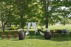 Ceremony set up with barrels, sidelights with curtains and eclectic seating for a small intimate backyard wedding