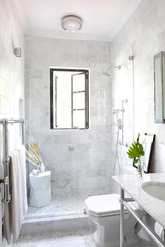 Amazing narrow bathroom features a seamless glass walk-in shower filled with white marble staggered tiles framing a French window next to a tiled niche and a white geometric stool over a marble hex shower floor.