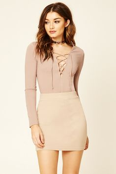 A long-sleeved knit crop top with a lace-up neckline.