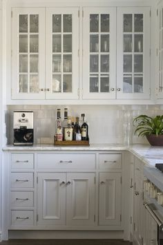 Phoebe Howard: Charming kitchen with glass-front upper kitchen cabinets filled with crystal wine ...