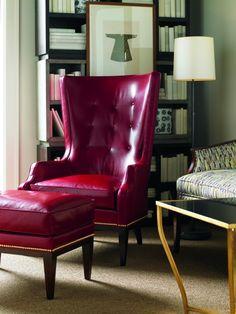 fauteuil bergère capitonné en cuir rouge, repose-pieds assorti et moquette beige